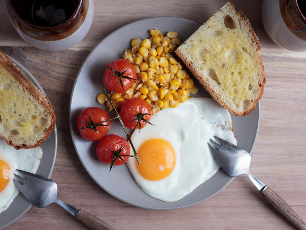 Creamed corn, fried egg and roast tomatoes